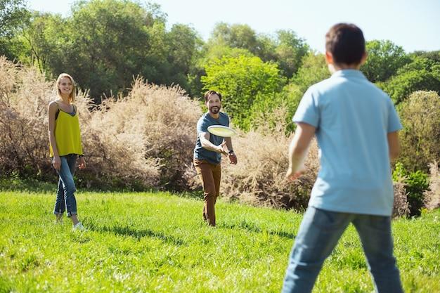Notre activité. joyeux papa barbu souriant tout en jouant à un jeu avec son fils et sa femme