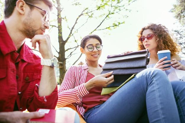 Notre décision. alerter une femme brune assise en plein air avec ses collègues et discutant de leur démarrage