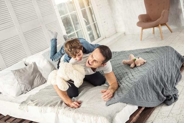 Notre jour de congé. beau papa aux cheveux noirs inspiré en riant et allongé sur le lit avec son fils et ils s'amusent