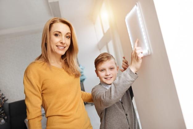 Notre maison. joyeux joyeux garçon intelligent debout avec sa mère et vous regarde tout en appuyant sur le bouton du panneau de commande