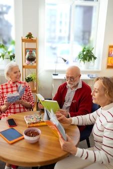 Notre passe-temps. de belles personnes âgées assises ensemble tout en participant au club de lecture