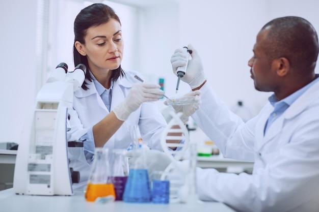 Notre recherche. chercheuse expérimentée inspirée effectuant un test et son collègue l'aidant
