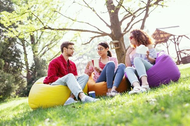 Notre travail. jolie femme concentrée assise en plein air avec ses collègues et discutant de leur projet