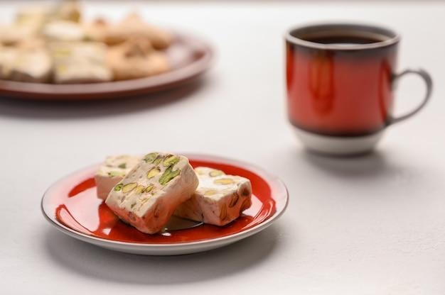 Nougat sur une assiette et une tasse de thé sur fond clair. mise au point sélective.