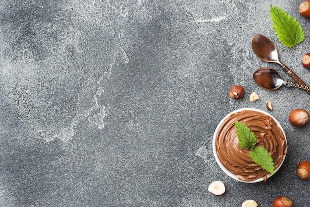 Nougat au chocolat dans une assiette sur un fond de béton foncé avec des noisettes.