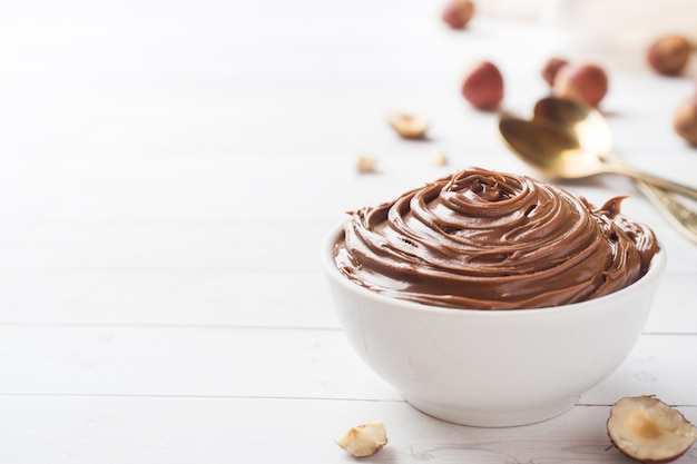 Nougat au chocolat dans une assiette sur un fond blanc avec des noisettes.