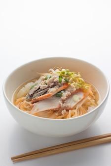 Nouilles asiatiques au poulet, légumes dans un bol, bois rustique.