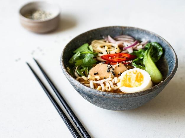 Nouilles asiatiques au ramen avec poulet, chou pak choi et œuf sur fond gris.