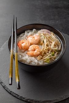 Nouilles asiatiques aux crevettes et fruits de mer dans un bol noir
