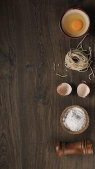 Nouilles asiatiques faites maison crues avec des œufs, du sel, des coquilles d'œufs et de la farine, espace de copie pour le papier peint ou les arrière-plans