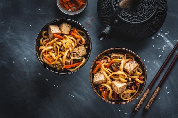 Nouilles asiatiques savoureuses avec du tofu au fromage et des légumes sur des assiettes.