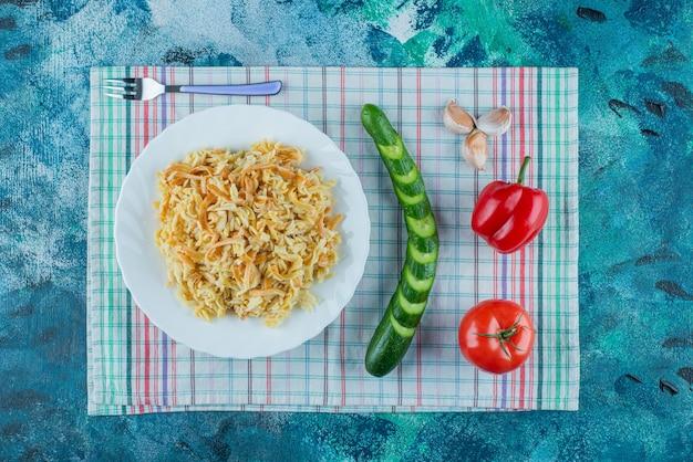 Nouilles sur une assiette à côté de divers légumes et fourchette sur un torchon, sur la table bleue.