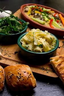 Nouilles au poisson sur une planche de bois, légumes à la crème, roquettes, petits pains à la tomate