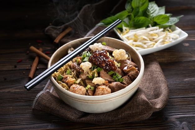 Nouilles au porc et boulettes de porc, pâte de piment avec soupe style thaï et légumes. nouilles de bateau. mise au point sélective