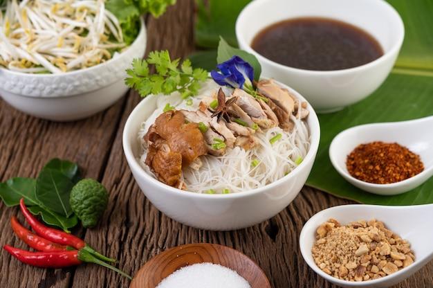 Nouilles au poulet dans un bol avec accompagnements, cuisine thaïlandaise