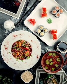 Nouilles au poulet sur la table avec des rouleaux de sushi