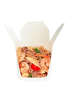 Nouilles au wok aux fruits de mer et légumes. dans une boîte d'expédition. ingrédients visibles. fermer. fond blanc. isolé.
