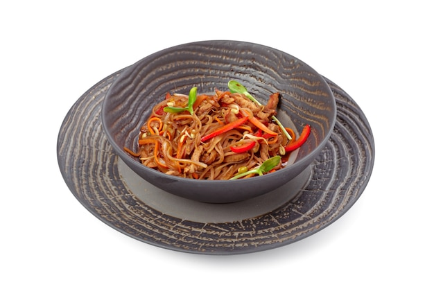 Nouilles au wok préparés avec des légumes en tranches sur la vaisselle grise