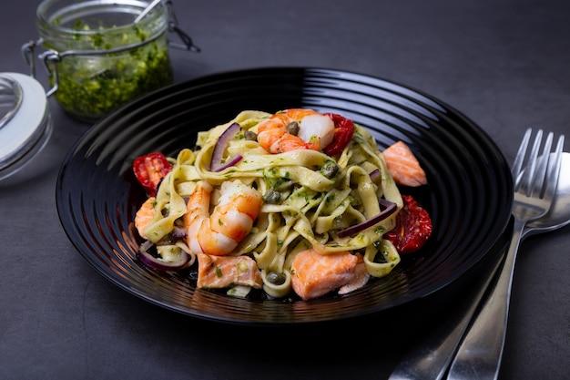 Nouilles aux fruits de mer, tomates séchées au soleil, câpres et oignons rouges. pâtes maison aux crevettes, saumon (truite) et sauce pesto. fond noir, plaque noire. fermer.