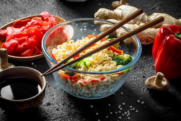 Nouilles aux légumes, gingembre et sauce soja. sur noir rustique