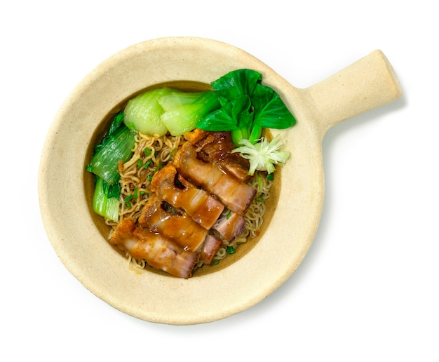Nouilles aux œufs avec du porc au ventre croustillant dans un pot en argile cuisine chinoise style asiatique décorer les légumes bok choy topview
