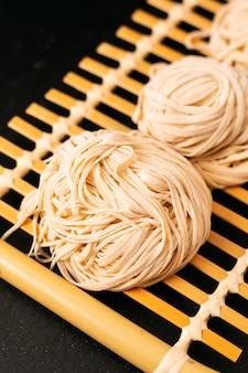 Nouilles aux oeufs orientales non cuites faites maison concept de cuisine asiatique sur un plateau en bambou avec espace de copie