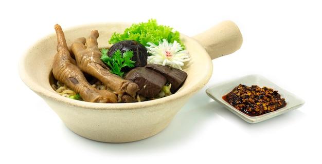 Nouilles aux œufs en pot d'argile avec pieds braisés au poulet décorent champignon sculpté poireau et légumes sideview