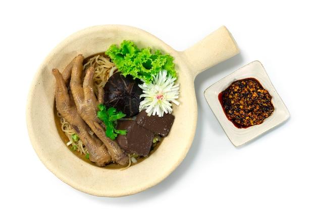 Nouilles aux œufs en pot d'argile avec pieds braisés au poulet décorent champignon sculpté poireau et légumes topview