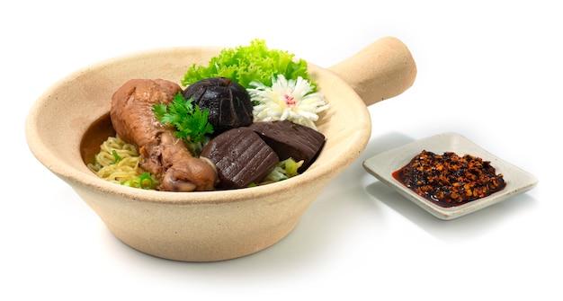 Nouilles aux œufs en pot d'argile avec poulet braisé aux pilons décorent champignon sculpté poireau et légumes sideview