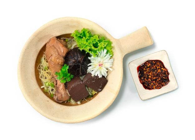 Nouilles aux oeufs en pot d'argile avec poulet braisé aux pilons décorent les champignons sculptés aux poireaux et aux légumes topview
