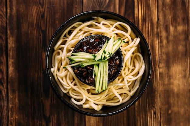 Nouilles aux oeufs ramen décorées de concombre dans un bol noir