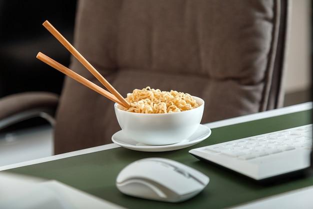Nouilles avec des baguettes sur le lieu de travail près d'un ordinateur portable pendant la pause déjeuner. la malbouffe pendant les heures supplémentaires. travailleur de bureau à domicile nourriture avec personne.