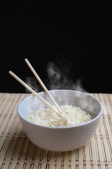 Nouilles de baguettes avec de la vapeur sur fond noir concept de malbouffe de nouilles asiatiques