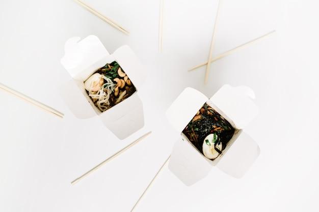 Nouilles en boîte et baguettes sur blanc