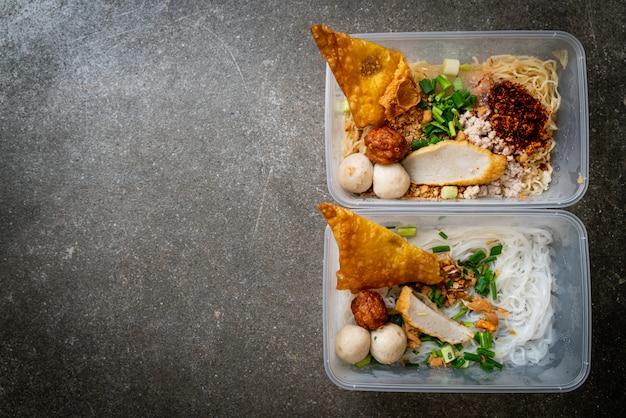 Nouilles avec boule de poisson et porc haché dans une boîte de livraison, style de cuisine asiatique
