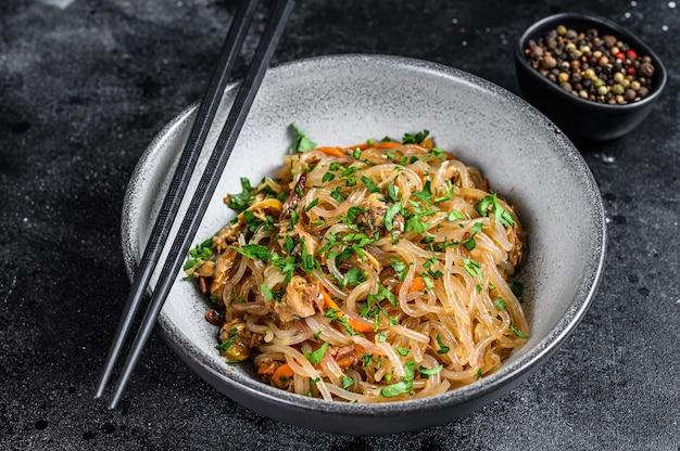 Nouilles de cellophane asiatiques chaudes au wok avec viande de poulet. fond noir. vue de dessus.