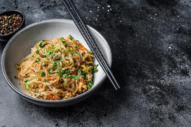 Nouilles de cellophane asiatiques chaudes au wok avec viande de poulet. vue de dessus.