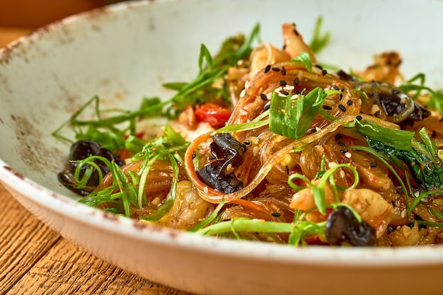 Nouilles cellophane aux crevettes et légumes, champignons shiitake dans une assiette blanche. wok de nouilles de riz