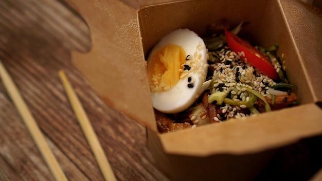 Nouilles chinoises au poulet et œuf dans une boîte en carton sur fond de bois, livraison de nourriture asiatique, concept de nourriture de rue, espace pour copie