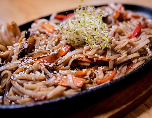 Nouilles chinoises aux moules et crevettes sur la table en bois.