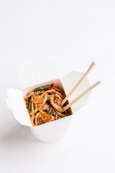 Nouilles chinoises avec des baguettes sur fond vide