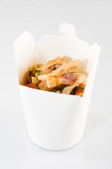 Nouilles chinoises en boîte blanche sur isolé avec un poulet et légumes