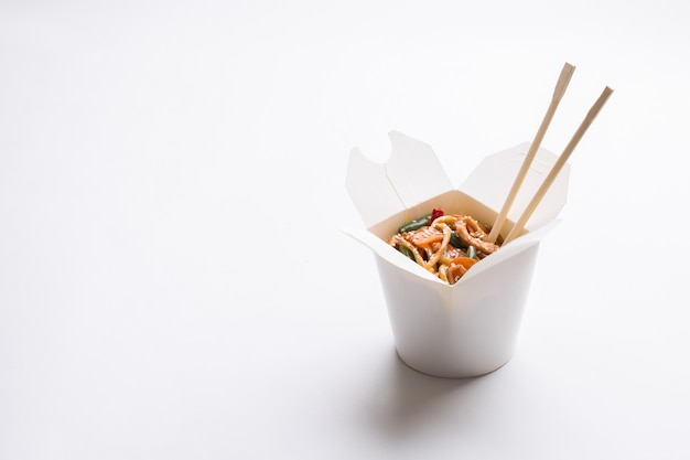 Nouilles chinoises dans une boîte blanche sur fond isolé
