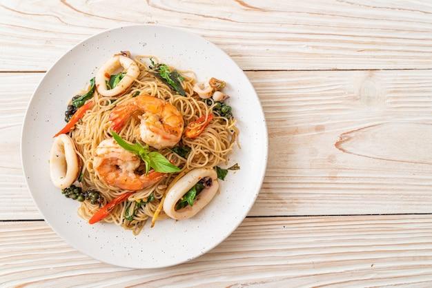 Nouilles chinoises sautées au basilic, piment, crevettes et calamars - cuisine asiatique