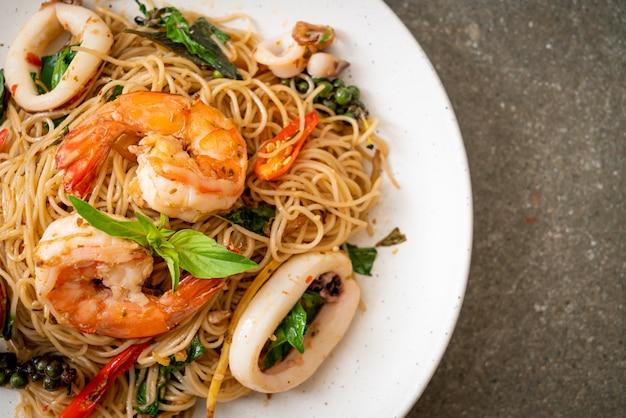 Nouilles chinoises sautées au basilic, piment, crevettes et calamars, style asiatique
