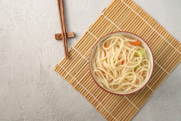Nouilles chinoises ou udon aux légumes et baguettes sur fond blanc isolé