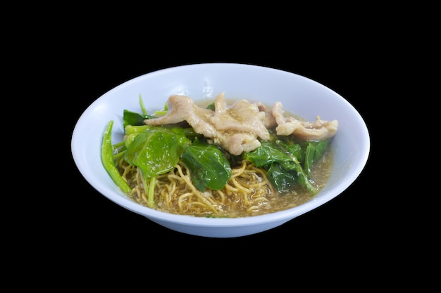 Nouilles croustillantes dans une sauce épaisse avec du porc et du chou chinois sur une surface noire