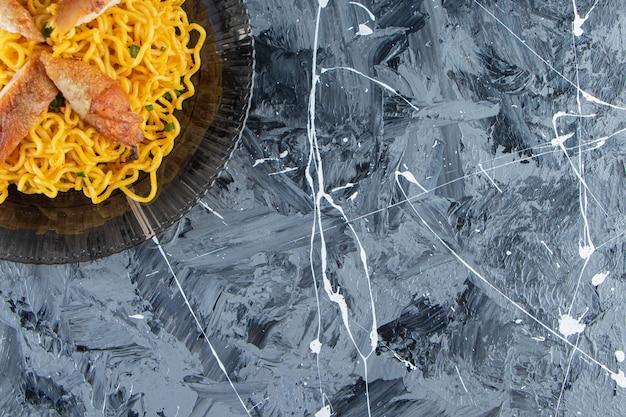 Nouilles cuites sur un plat en verre, sur fond de marbre.
