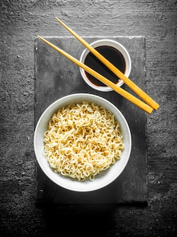 Nouilles dans un bol sur une planche de pierre avec de la sauce soja et des baguettes sur table rustique noire.
