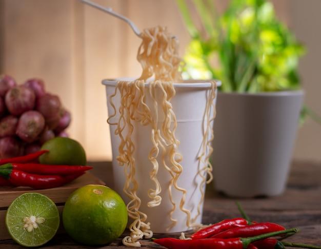 Nouilles dans une tasse blanche avec citron vert et piment et oignon et légumes sur table en bois